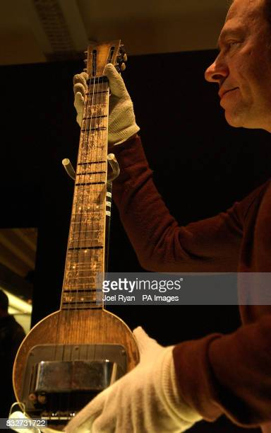 A Harrods worker holds the 1931 'Frying Pan' the worlds first electric guitar carved from one piece of wood as valuable electric guitars arrive in a...