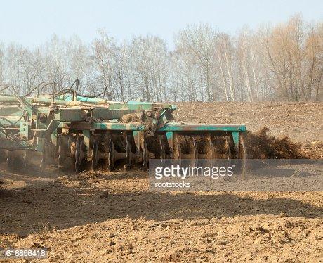 Harrowing the soil with disc harrows : Stock Photo