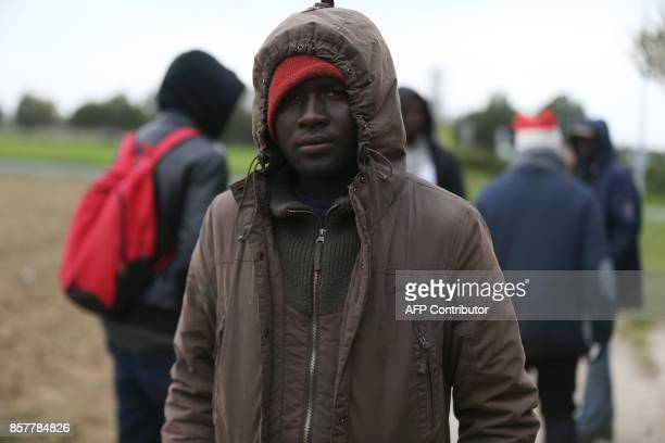 Harry a Sudanese migrant and others wait on the side of a road in Ouistreham near Caen northwestern France on October 5 2017 Migration is a hot...
