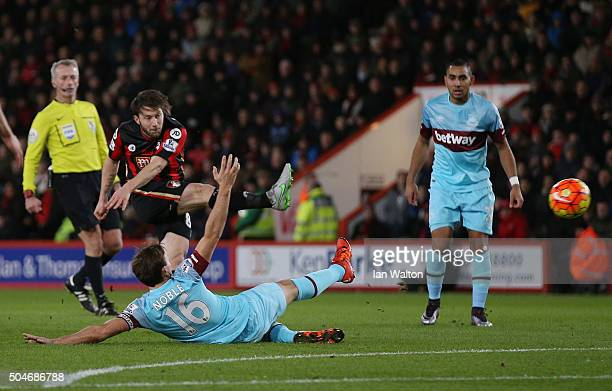 Harry Arter of Bournemouth shoots past Mark Noble of West Ham United as he scores their first goal during the Barclays Premier League match between...