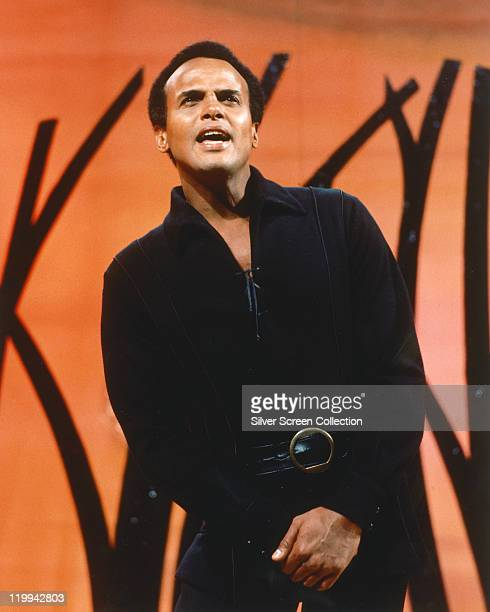 Harry Belafonte US singer and actor wearing a black outfit as he sings with his hands clasped together in front circa 1965