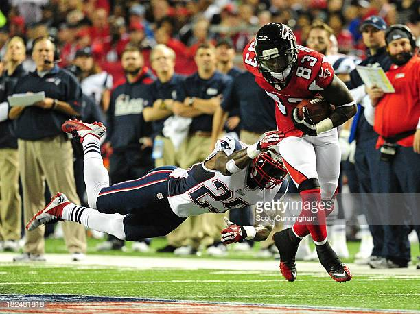 Harry Douglas of the Atlanta Falcons runs with a catch against Kyle Arrington of the New England Patriots at the Georgia Dome on September 29 2013 in...