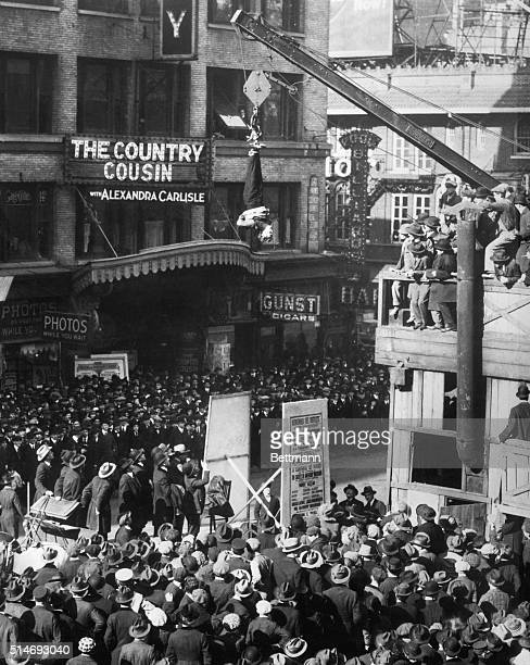 Harry Houdini American magician slipping out of a straitjacket while hanging upside down over Broadway and 46th street in New York City