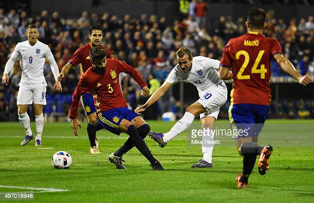 Harry Kane of England shoots past Gerard Pique of Spain during the international friendly match between Spain and England at Jose Rico Perez Stadium...