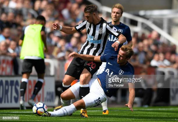 Harry Kane of Tottenham Hotspur fouls Florian Lejeune of Newcastle United and recives a yellow card during the Premier League match between Newcastle...