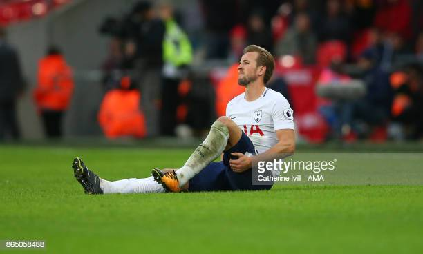 Harry Kane of Tottenham Hotspur holds his leg as he sits on the pitch during the Premier League match between Tottenham Hotspur and Liverpool at...