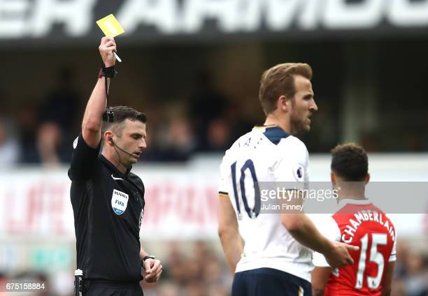 Harry Kane of Tottenham Hotspur is shown a yellow card by referee Michael Oliver during the Premier League match between Tottenham Hotspur and...