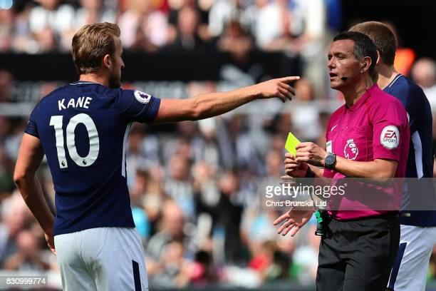 Harry Kane of Tottenham Hotspur is shown a yellow card by Referee Andre Marriner during the Premier League match between Newcastle United and...