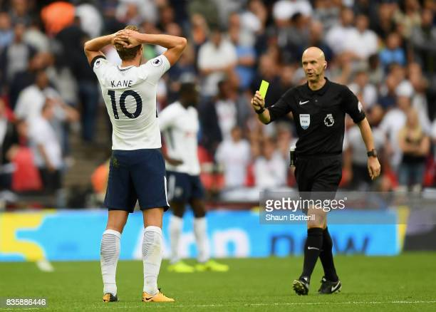 Harry Kane of Tottenham Hotspur is shown a yellow card by referee Anthony Taylor during the Premier League match between Tottenham Hotspur and...