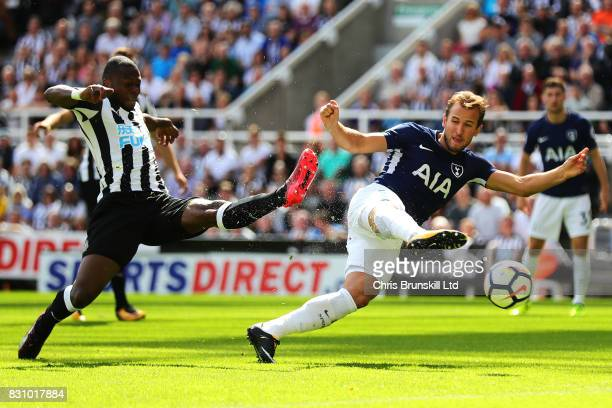 Harry Kane of Tottenham Hotspur shoots at goal under pressure from Chancel Mbemba of Newcastle United during the Premier League match between...