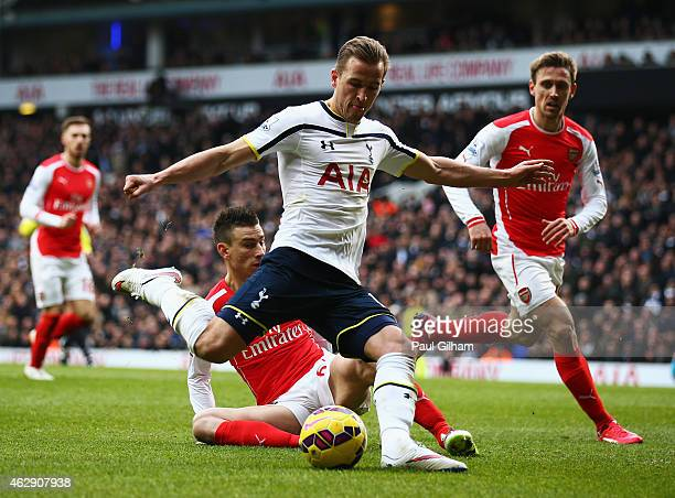 Harry Kane of Tottenham Hotspur shoots under pressure from Laurent Koscielny and Nacho Monreal of Arsenal during the Barclays Premier League match...