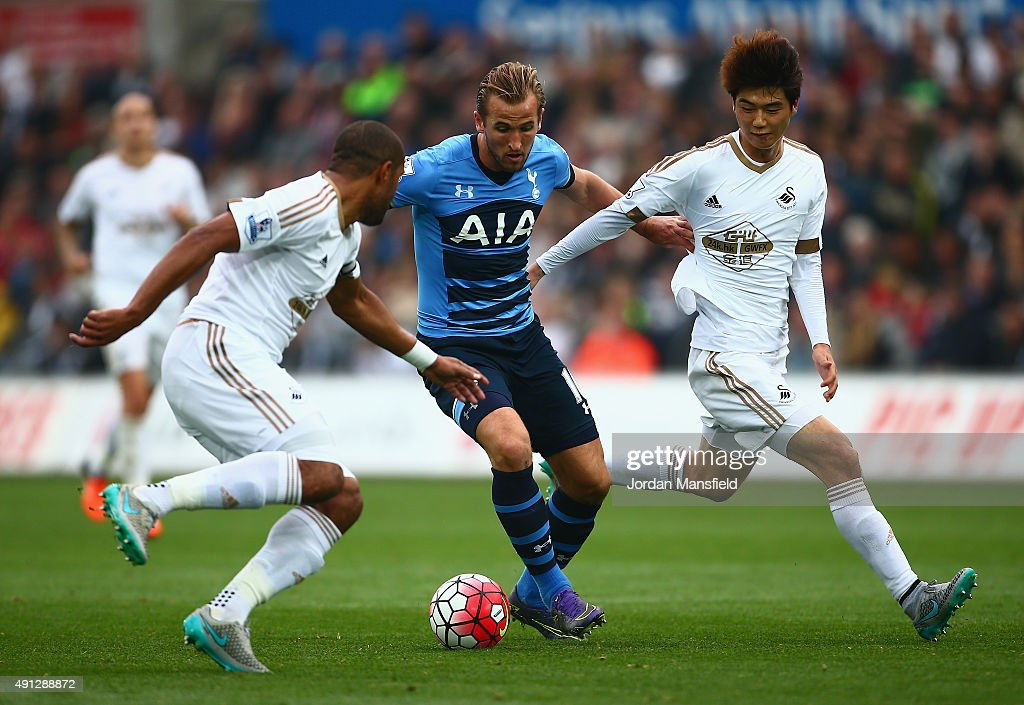 Harry Kane of Tottenham Hotspur takes on Ashley Williams of Swansea City and Ki Sung-Yeung of Swansea City during the Barclays Premier League match between Swansea City and Tottenham Hotspur at Liberty Stadium on October 4, 2015 in Swansea, Wales.