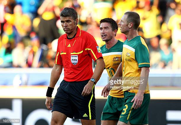 Harry Kewell and Craig Moore of Australia argue with the referee Roberto Rosetti after he sends off Kewell for handball and awards Ghana a penalty...