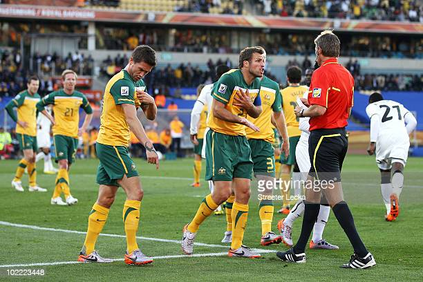 Harry Kewell of Australia explains the ball hit his arm and Lucas Neill pleads with the referee as Roberto Rosetti sends off Kewell for handball and...