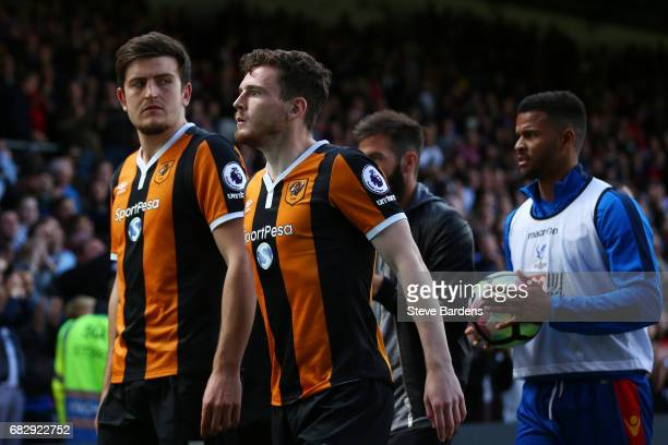 Harry Maguire of Hull City and Andrew Robertson of Hull City leave the pitch looking dejected after being relegated to the Championship after the...