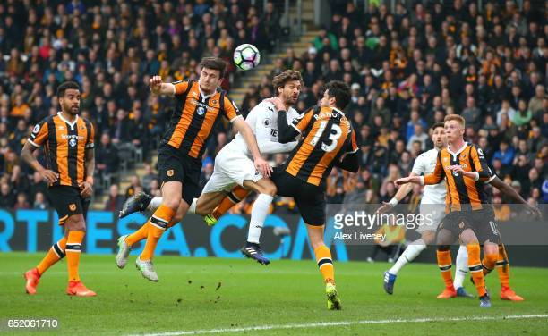 Harry Maguire of Hull City Fernando Llorente of Swansea City and Andrea Ranocchia of Hull City battle to win a header during the Premier League match...