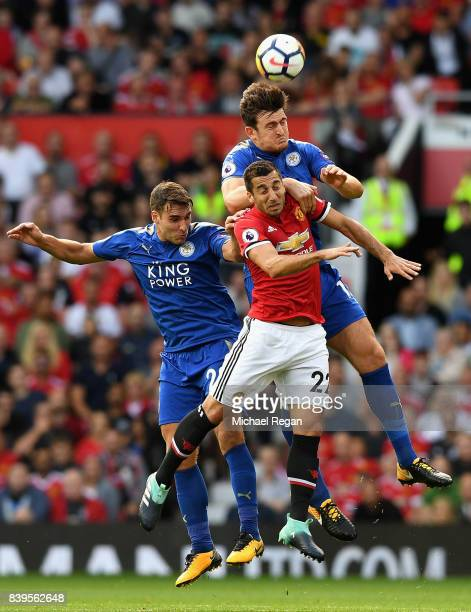 Harry Maguire of Leicester City and Henrikh Mkhitaryan of Manchester United battle for possession in the air during the Premier League match between...