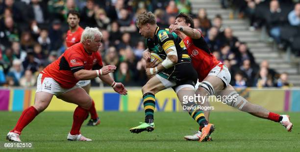 Harry Mallinder of Northampton is tackled by Petrus du Plessis and Michael Rhodes during the Aviva Premiership match between Northampton Saints and...