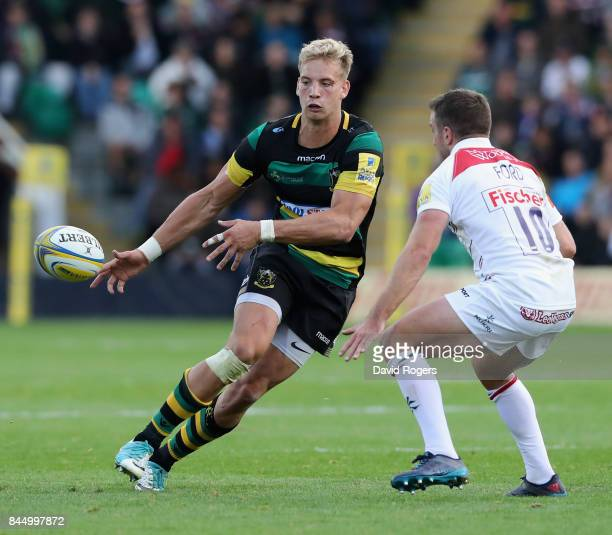 Harry Mallinder of Northampton off loads the ball watched by George Ford during the Aviva Premiership match between Northampton Saints and Leicester...