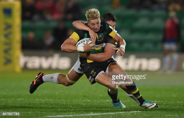Harry Mallinder of Northampton Saints is tackled by Charlie Ewels of Bath Rugby during the Aviva Premiership match between Northampton Saints and...