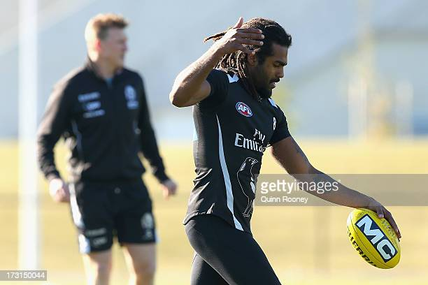 Harry O'Brien of the Magpies trains as Nathan Buckley the coach of the Magpies looks on behind during a Collingwood Magpies AFL training session at...