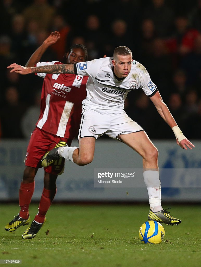 Harry Pell (R) of Hereford United powers his way past Jermaine McGlashan (L) of Cheltenham Town during the FA Cup with Budweiser Second Round match between Cheltenham Town and Hereford United at the Abbey Business Stadium on December 3, 2012 in Cheltenham, England.
