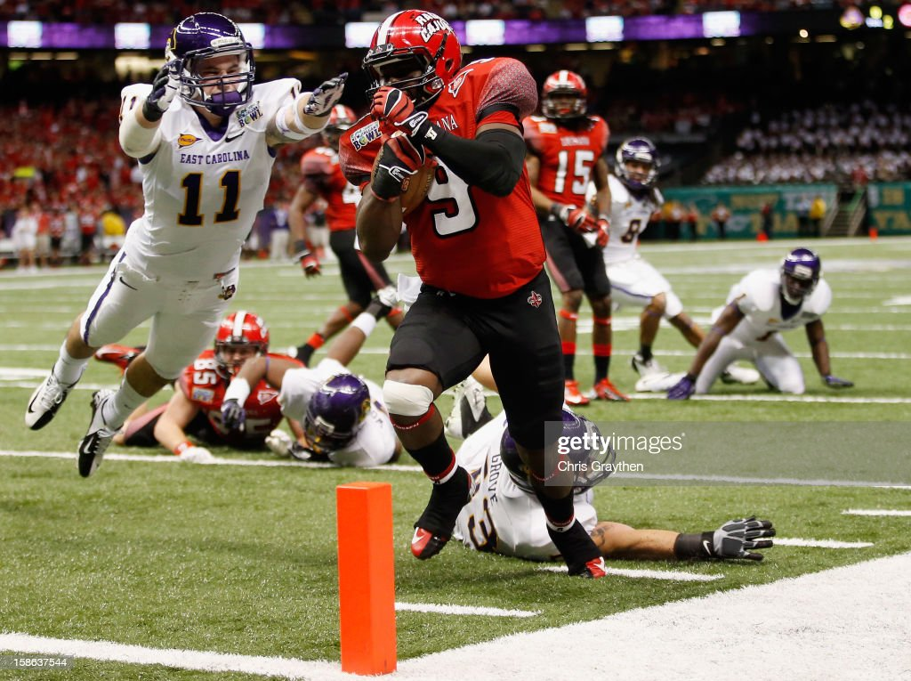 Harry Peoples #9 of the Louisiana-Lafayette Ragin Cajuns scores a touchdown over Damon Magazu #11 of the East Carolina Pirates during the R+L Carriers New Orleans Bowl at the Mercedes-Benz Superdome on December 22, 2012 in New Orleans, Louisiana.