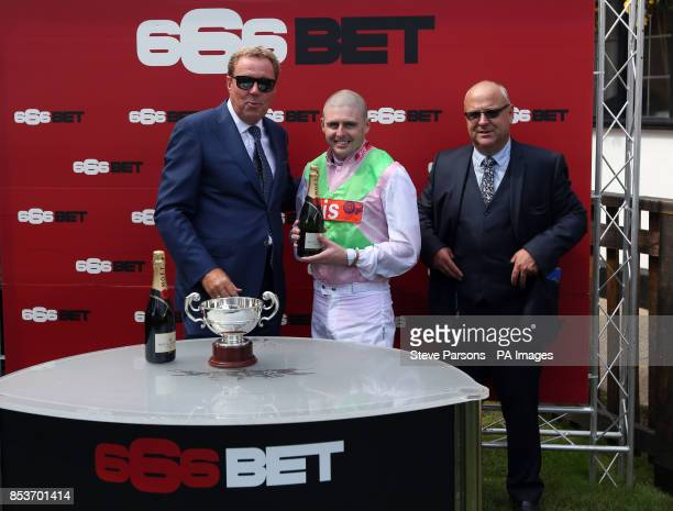 Harry Redknapp presents the trophy to jockey Tony Hamilton after Heaven's Guest's victory in the 666bet Bunbury Cup as trainer Richard Fahey looks on