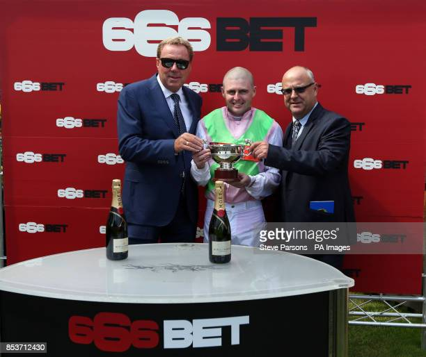 Harry Redknapp presents the winning trophy to Heaven's Guest jockey Tony Hamilton and trainer Richard Fahey after winning the 666BET Burbury cup...