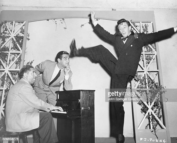 Harry Revel and composer Mort Greene watch Ray Bolger rehearsing an intricate dance step to the tune of I'm in Fine Shape For the Shape I'm In for...