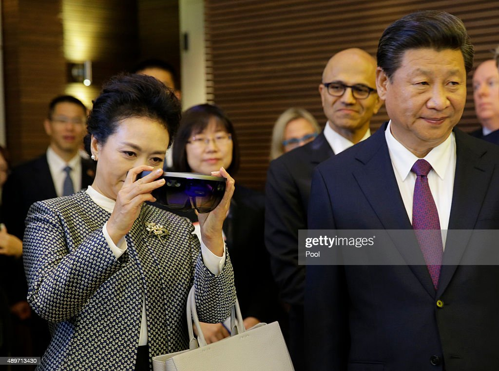 Peng Liyuan left stands next to her husband Chinese President Xi Jinping as she examines Micosoft's HoloLens device during a tour of Microsoft's main...