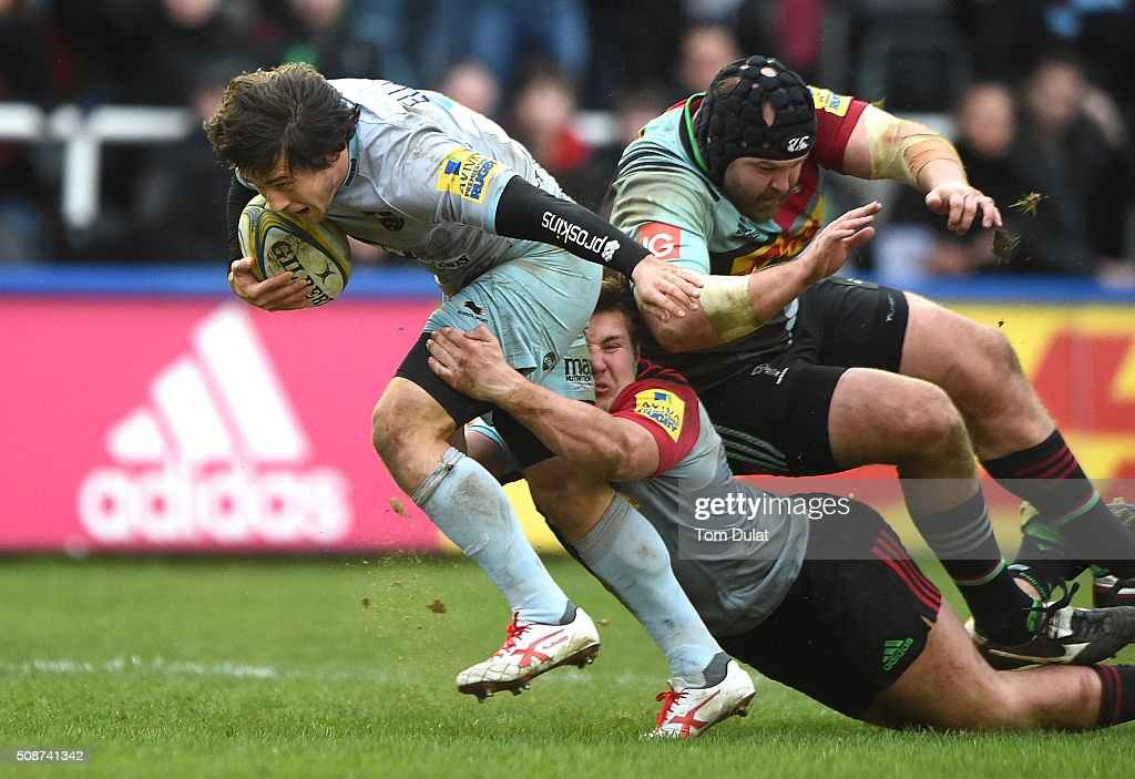 Harry Sloan (L) and Mark Lambert (R) of Harlequins tackle Jamie Elliott of Northampton Saints during the Aviva Premiership match between Harlequins and Northampton Saints at Twickenham Stoop on February 6, 2016 in London, England. (Photo by Tom Dulat/Getty Images).