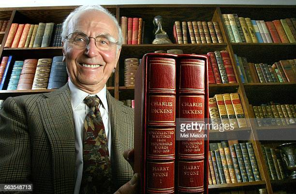 Harry Stone retired professor of english at Cal State University Northridge holds up a 2 volume set of Charles Dickens books called 'Uncollected...