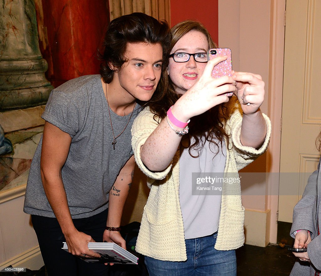 <a gi-track='captionPersonalityLinkClicked' href=/galleries/search?phrase=Harry+Styles&family=editorial&specificpeople=7229830 ng-click='$event.stopPropagation()'>Harry Styles</a> of One Direction poses for a picture with a fan as he attends the book signing of One Direction's new book 'Where We Are' held at Alexandra Palace on November 18, 2013 in London, England.