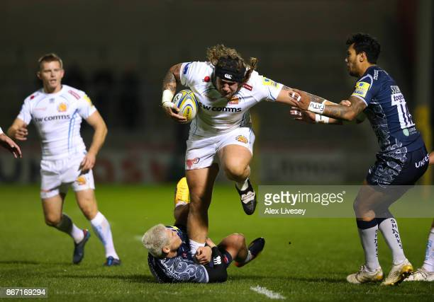 Harry Williams of Exeter Chiefs is tackled by James OConnor and Denny Solomona of Sale Sharks during the Aviva Premiership match between Sale Sharks...