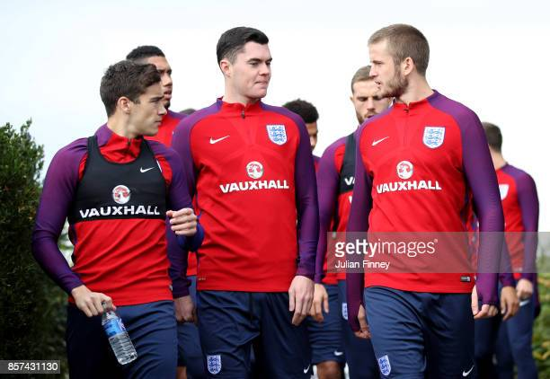Harry Winks of England Michael Keane of England and Eric Dier of England speak as they walk out prior to a England Training Session at the Tottenham...
