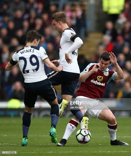 Harry Winks of Tottenham Hotspur Christian Eriksen of Tottenham Hotspur and Joey Barton of Burnley battle for possession during the Premier League...