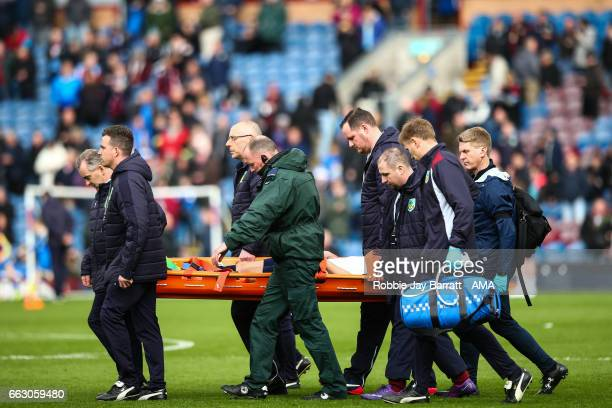 Harry Winks of Tottenham Hotspur gets carried off injured at half time during the Premier League match between Burnley and Tottenham Hotspur at Turf...