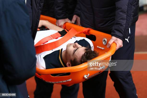 Harry Winks of Tottenham Hotspur is taken off injured on a stretcher during the Premier League match between Burnley and Tottenham Hotspur at Turf...