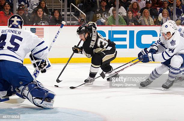 Harry Zolnierczyk of the Pittsburgh Penguins moves the puck between Jonathan Bernier and Morgan Rielly of the Toronto Maple Leafs on December 16 2013...