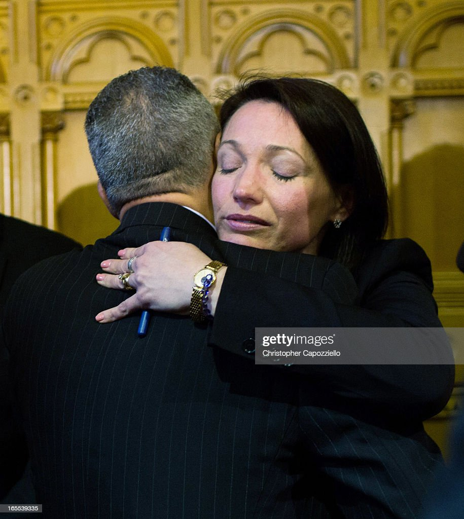 Hartford Mayor Pedro Segarra (L) hugs Nicole Hockley, the parent of a Sandy Hook shooting victim, after the signing of a gun control law at the Connecticut Capitol pril 4, 2013 in Hartford, Connecticut, After more than 13 hours of debate, the Connecticut General Assembly approved the gun-control bill early April 4, that proponents see as the toughest-in-the-nation response to the Demember 14, 2012 Newtown school shootings.