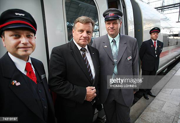 Hartmut Mehdorn chairman of Germany's stateowned rail operator Deutsche Bahn poses between German train conductor Antonio Gimmilano and his French...