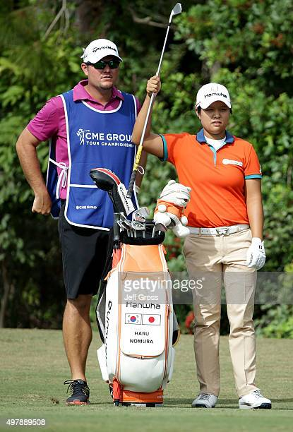 Haru Nomura of Japan pulls a club from her bag as her caddie looks on from the first fairway during the first round of the CME Group Tour...