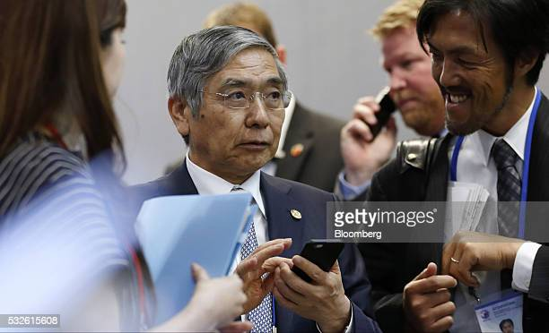 Haruhiko Kuroda governor of the Bank of Japan center holds a smartphone as he arrives for the welcome reception for the Group of Seven finance...