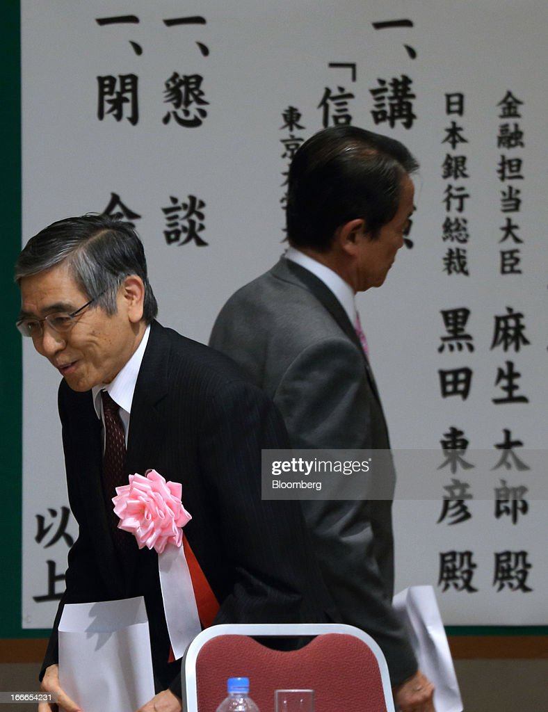 Haruhiko Kuroda, governor of the Bank of Japan (BOJ), left, bows as Taro Aso, Japan's deputy prime minister and finance minister, leaves the annual meeting of the Trust Companies Association of Japan in Tokyo, Japan, on Monday, April 15, 2013. Kuroda reiterated today that he has a two-year time horizon in mind for achieving his inflation goal. He will also speak today at the annual meeting. Photographer: Tomohiro Ohsumi/Bloomberg via Getty Images
