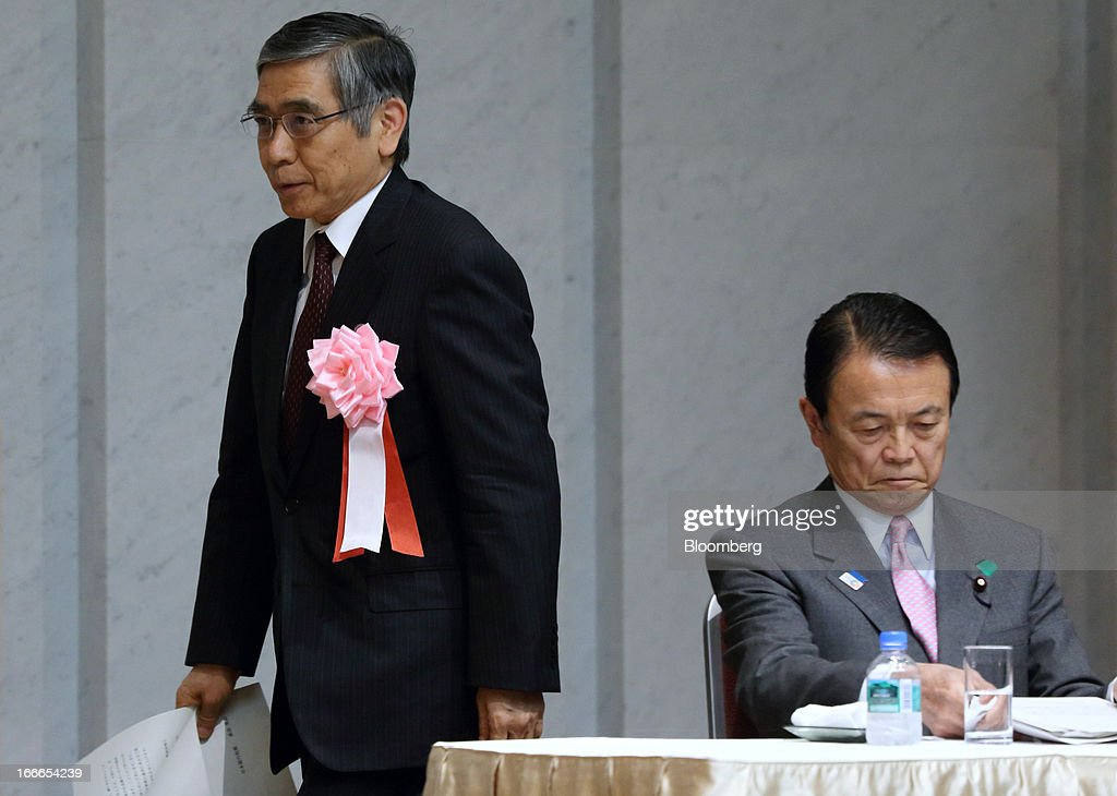 Haruhiko Kuroda, governor of the Bank of Japan (BOJ), left, walks past Taro Aso, Japan's deputy prime minister and finance minister, as he walks to the podium at the annual meeting of the Trust Companies Association of Japan in Tokyo, Japan, on Monday, April 15, 2013. Kuroda reiterated today that he has a two-year time horizon in mind for achieving his inflation goal. He will also speak today at the annual meeting. Photographer: Tomohiro Ohsumi/Bloomberg via Getty Images