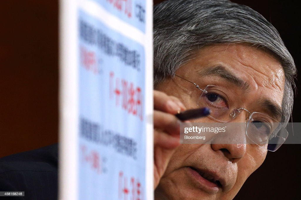 Haruhiko Kuroda, governor of the Bank of Japan (BOJ), points to a sign as he speaks during a news conference at the central bank's headquarters in Tokyo, Japan, on Friday, Oct. 31, 2014. Kuroda led a divided board to expand what was already an unprecedentedly large monetary-stimulus program, boosting stocks and sending the yen tumbling. Photographer: Tomohiro Ohsumi/Bloomberg via Getty Images