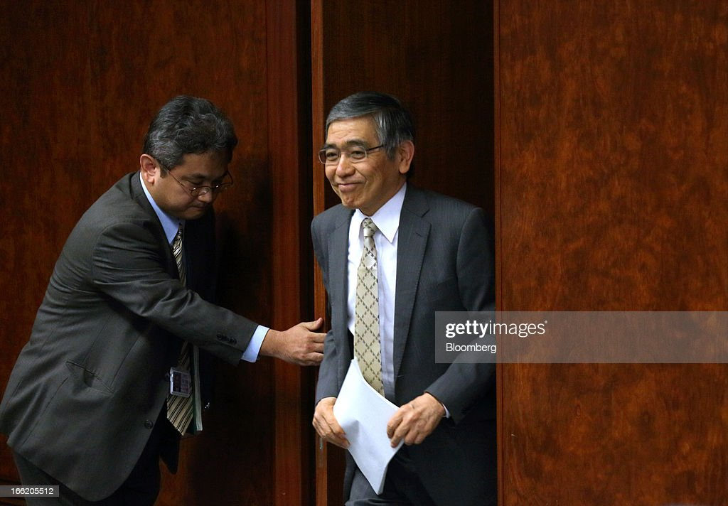 Haruhiko Kuroda, governor of the Bank of Japan (BOJ), right, arrives for a group interview at the central bank's headquarters in Tokyo, Japan, on Wednesday, April 10, 2013. Kuroda said that the central bank will take all measures necessary to meet a 2 percent inflation target even as he indicated policy adjustments are unlikely every month. Photographer: Tomohiro Ohsumi/Bloomberg via Getty Images