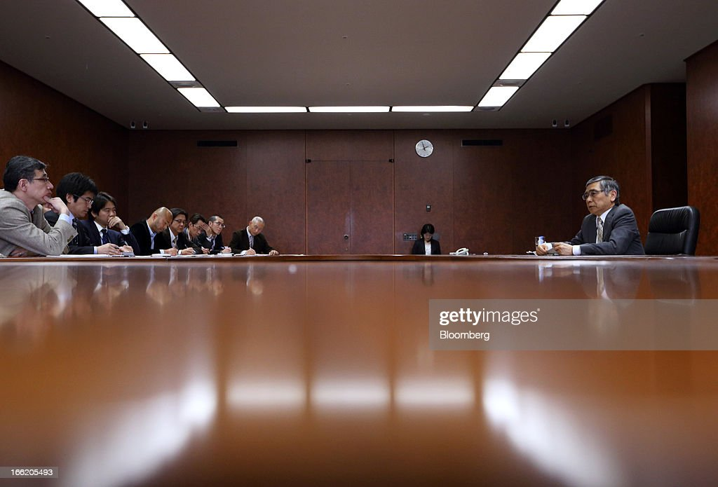 Haruhiko Kuroda, governor of the Bank of Japan (BOJ), right, speaks during a group interview at the central bank's headquarters in Tokyo, Japan, on Wednesday, April 10, 2013. Kuroda said that the central bank will take all measures necessary to meet a 2 percent inflation target even as he indicated policy adjustments are unlikely every month. Photographer: Tomohiro Ohsumi/Bloomberg via Getty Images