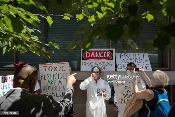 Harvard Club employee asks environmental activists to remove signage from the building during a protest outside of the Harvard Club where...